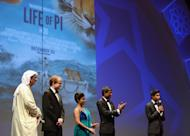 """DUBAI, UNITED ARAB EMIRATES - DECEMBER 09: Artistic Director of DIFF Masoud Amralla Al Ali, guest and actors Shravanthi Sainath, Adil Hussain and Suraj Sharma on stage ahead of the """"Life of PI"""" Opening Gala during day one of the 9th Annual Dubai International Film Festival held at the Madinat Jumeriah Complex on December 9, 2012 in Dubai, United Arab Emirates. (Photo by Andrew H. Walker/Getty Images for DIFF)"""