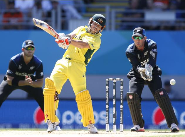 Australia's David Warner hits out while being watched by New Zealand's Corey Anderson and Luke Ronchi in their Cricket World Cup match in Auckland
