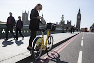 LONDON, ENGLAND - APRIL 15: A woman stands with her specially painted yellow London Cycle Hire scheme bike on Westminster Bridge on April 15, 2014 in London, England. 101 of the capital's 10,000 Cycle Hire bikes have been painted yellow to mark 100 days until the 101st Tour de France arrives in London on July 7, 2014. (Photo by Oli Scarff/Getty Images)