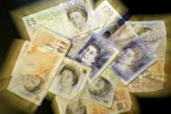 British Sterling pound notes are pictured in London. Fitch lowered Britain's long-term outlook Wednesday to negative from stable, while confirming its top-level AAA rating