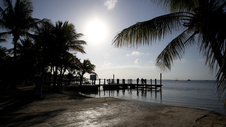 In this Feb. 12, 2013 photo,visitors to Key Largo, Fla., stand on a pier and watch the sunset. If you're heading south into the Keys from the Miami or Fort Lauderdale areas, Key Largo is the first island you hit. State parks offer great opportunities for birdwatching and nature photography.  (AP Photo/J Pat Carter)