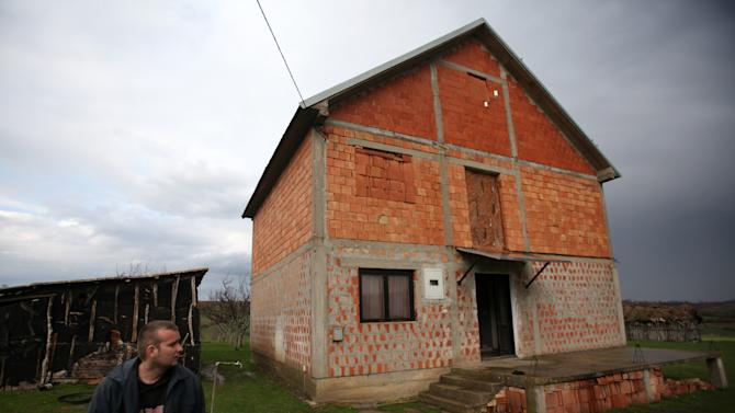 Aleksandar Stekic stands in front house where his mother Dragana was shot to death while sleeping in the village of Velika Ivanca, Serbia, Tuesday, April 9, 2013. A 60-year-old man gunned down 13 people, including a baby, in a house-to-house rampage in a quiet village on Tuesday before trying to kill himself and his wife, police and hospital officials said. Belgrade emergency hospital spokeswoman Nada Macura said the man, identified as Ljubisa Bogdanovic, used a handgun in the shooting spree at five houses. The dead included six women. (AP Photo/Darko Vojinovic)