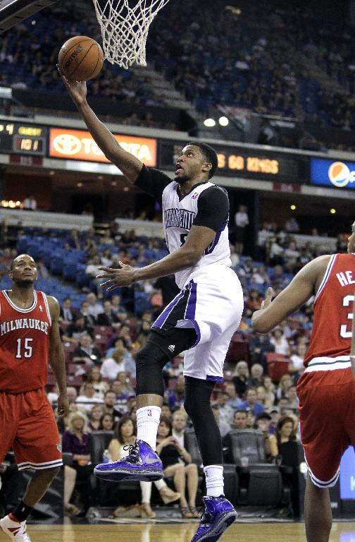 Sacramento Kings forward Rudy Gay, center, drives to the basket between Milwaukee Bucks' Chris Wright, left, and John Henson during the fourth quarter of an NBA basketball game in Sacramento, Calif., Sunday, March 23, 2014. The Kings won 124-107