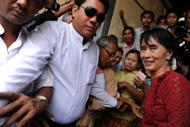 Myanmar opposition leader Aung San Suu Kyi (R) is surrounded by supporters and journalists as she leaves a polling station in the constituency where she is standing as a candidate in Kawhmu on April 1, 2012