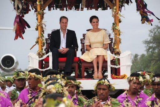 Britain's Prince William (L) and his wife Catherine (R), the Duchess of Cambridge, are carried on thrones