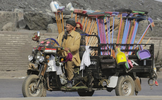 An Egyptian broom vender drives his motorized tricycle in Cairo, Egypt, Wednesday, March 4, 2015. Egypt is scheduled to host the Egypt Economic Development Conference in the Red Sea resort of Sharm El