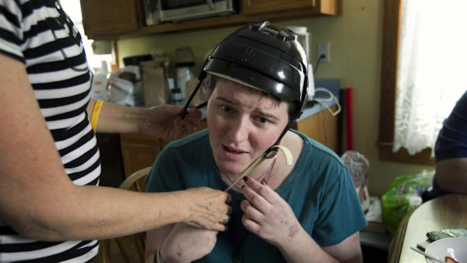 In this Thursday, Aug. 2, 2012 photo, Meg Theriault is helped with a helmet by her mother, Deb Theriault, left, as she talks with her family about the logistics of her daily life recovering from a traumatic brain injury at their home in Salisbury, Mass. It was the first time at home for Meg since being involved in a multi-fatal minivan accident in New Zealand, May 12, 2012, that killed three Boston University students. (AP Photo/Steven Senne)