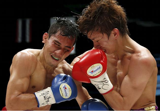 Taguchi punches Sithmorseng during their light flyweight boxing title bout in Tokyo