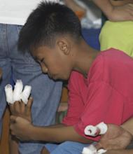 A Filipino boy looks at his injured hands following his treatment after sustaining injuries from firecrackers at New Year at Manila's Rizal Park, Philippines on Sunday Jan. 1, 2012. More than 200 people have been injured by illegal firecrackers and celebratory gunfire in the Philippines despite a government scare campaign against reckless New Year revelries, officials recently said. (AP Photo/Aaron Favila)