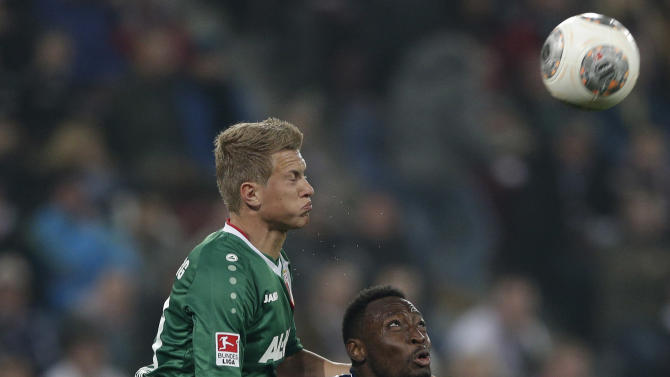 Augsburg's Matthias Ostrzolek, left, and Schalke's Chinedu Obasi of Nigeria challenge for the ball during the German first division Bundesliga soccer match between FC Augsburg and FC Schalke 04, in Augsburg, southern Germany, Friday, March 14, 2014