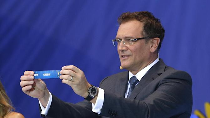 FIFA Secretary General Jerome Valcke shows the ticket of Greece during the draw ceremony for the 2014 soccer World Cup in Costa do Sauipe near Salvador, Brazil, Friday, Dec. 6, 2013