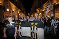 Juventus' supporters celebrate on May 6, in central Turin, at the end of the Serie A match Juventus against Cagliari held at Nereo Rocco stadium in Trieste. Juventus won the match 2-0 to win the Italian championship