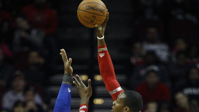 Houston Rockets power forward Dwight Howard (12) shoots over Orlando Magic power forward Glen Davis (11)during the first quarter of an NBA basketball game Sunday, Dec. 8, 2013, in Houston