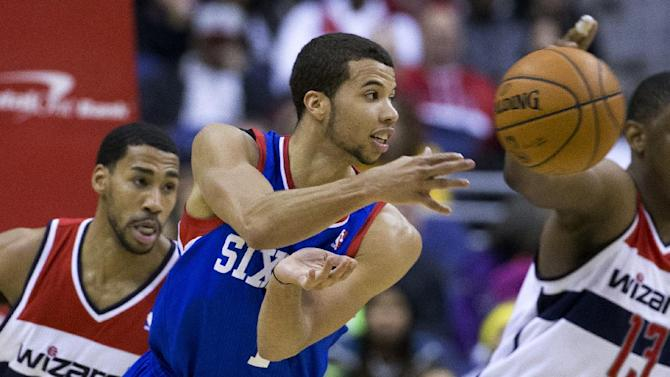 Washington Wizards shooting guard Garrett Temple, left, looks on as Philadelphia 76ers point guard Michael Carter-Williams delivers a pass during the second half of an NBA basketball game on Monday, Jan. 20, 2014 in Washington. The Wizards defeated the 76ers 107-99