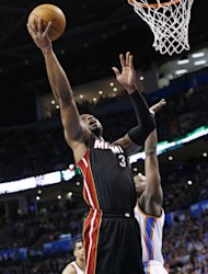 Miami Heat guard Dwyane Wade (3) shoots in front of Oklahoma City Thunder guard Reggie Jackson (15) during the first quarter of an NBA basketball game in Oklahoma City, Thursday, Feb. 20, 2014. (AP Photo/Sue Ogrocki)