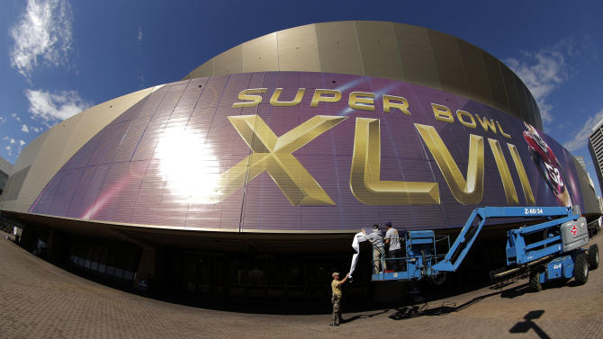 In this photo taken with a fisheye lens, workers put up signage outside the Superdome where tomorrow's NFL Super Bowl XLVII football game between the San Francisco 49ers and Baltimore Ravens will be played, Saturday, Feb. 2, 2013, in New Orleans. (AP Photo/Charlie Riedel)