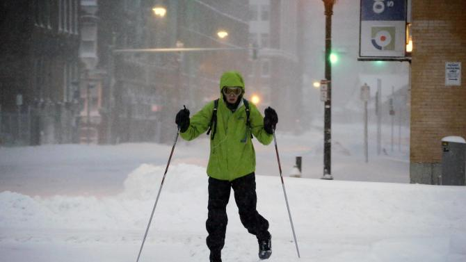 A pedestrian uses skis to travel through the deserted snow-covered streets of Boston early Saturday, Feb. 9, 2013. (AP Photo/Gene J. Puskar)