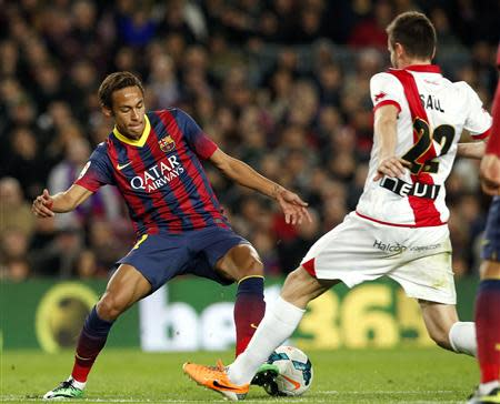 Barcelona's Neymar fights for the ball against Rayo Vallecano's Saul Niguez during their Spanish first division soccer match in Barcelona