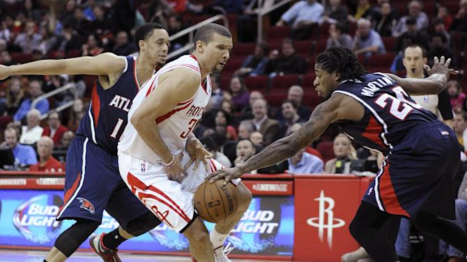 Atlanta Hawks' Cartier Martin (20) knocks the ball away from Houston Rockets' Francisco Garcia (32) as John Jenkins (12) crowds in in the second half of an NBA basketball game Wednesday, Nov. 27, 2013, in Houston. The Rockets won 113-84