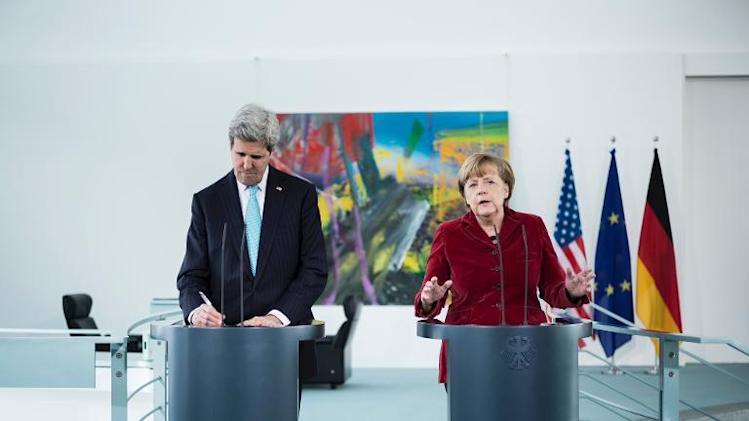 US Secretary of State John Kerry (L) takes notes as German Chancellor Angela Merkel (R) addresses the press before a meeting at the Chancellery January 31, 2014 in Berlin, Germany