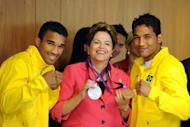 "Brazilian President Dilma Rousseff (C) poses with Olympic boxers Yamaguchi Falcao (R) and Esquiva Falcao (L) and their medals. Rousseff received the Olympic flag on Tuesday as the competition's world governing body warned that the country had to ""work harder"" ahead of the Rio 2016 Summer Games"
