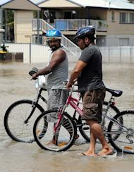 This file photo shows residents walking with their bicycles through floodwater in Rockhampton, on January 6, 2011. Authorities say there were 20 water rescue cases across central Queensland state overnight and early Friday, after the remnants of tropical cyclone Oswald dumped huge rains around Rockhampton
