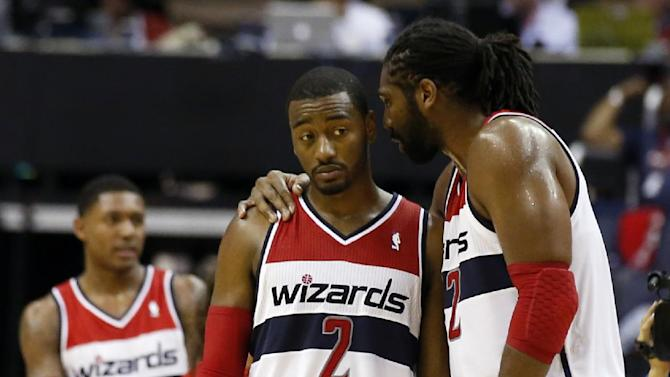 Washington Wizards guard John Wall (2) listens to forward Nene (42), from Brazil, during a timeout in the second period of an NBA basketball game against the Cleveland Cavaliers, Saturday, Nov. 16, 2013, in Washington. The Cavaliers won 103-96 in overtime