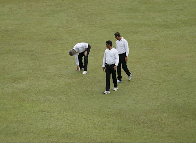 Umpire Llong inspects the ground condition next to umpire Tucker and Palliyaguruge after the rain, on the first day of third and final test cricket match between India and Sri Lanka in Colombo