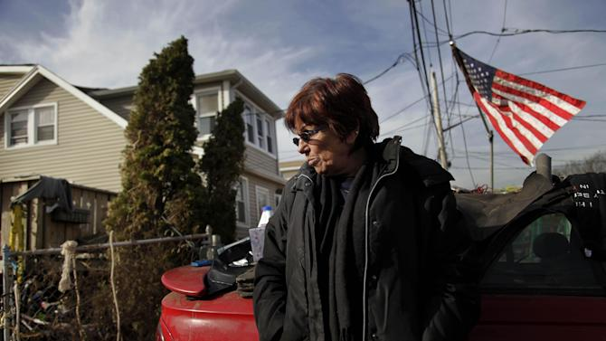 "FILE - In this Nov. 20, 2012 file photo, Marge Gatti stands in front of her home, which was damaged by Superstorm Sandy, in the Midland Beach section of the Staten Island borough of New York. Six months after the storm, Gatti, the matriarch of her family, said ""The whole family's separated, and it's terrible, you know?"" The flood-soaked place was demolished months ago, and they're waiting for a government buyout. Now the family is scattered across New Jersey, New York and Texas.   (AP Photo/Seth Wenig, File)"