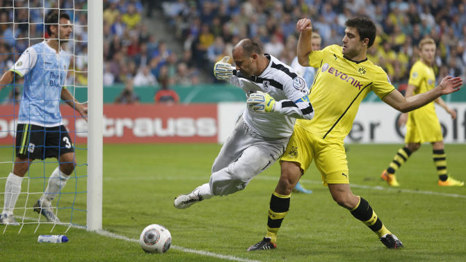 Munich's Garbor Kiraly and Dortmund's Sokratis of Greece, right, challenge for the ball during the German soccer cup second round match between TSV 1860 Munich and Borussia Dortmund, in Munich, southern Germany, Tuesday, Sept. 24, 2013