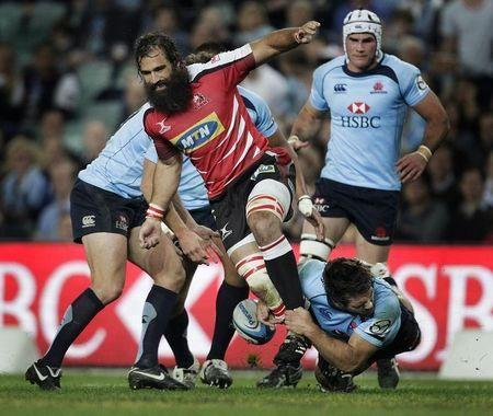 Strauss of the Lions is tackled by Alcock of the Waratahs during their Super 15 rugby union match in Sydney