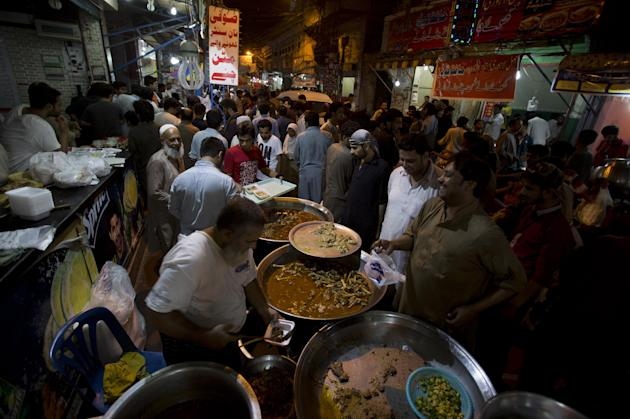 People buy food for 'sehri', the pre-dawn meal for Muslims observing Ramadan, in Rawalpindi, Pakistan, Tuesday, July 7, 2015. Muslims across the world are observing the holy fasting month of R