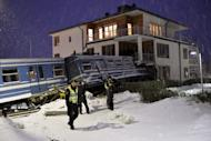Swedish police stand in front of a commuter train that derailed into a residential building in Saltsjoebaden, on January 15, 2013. A Swedish cleaning lady commandeered an empty Stockholm commuter train, which careered off the tracks when it reached the end of the line and smashed into a block of flats, police said