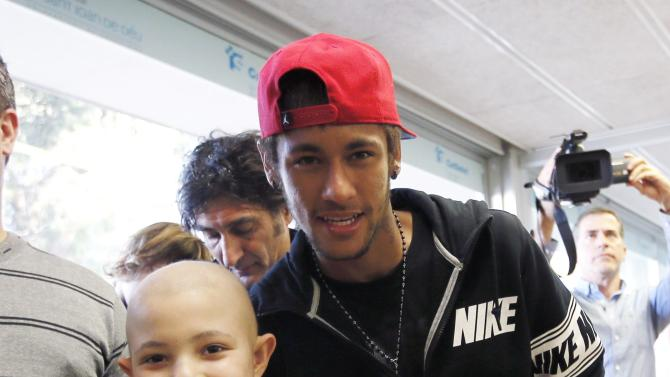Barcelona soccer player Neymar poses with a child during a charity visit to the Hospital Sant Joan de Deu in Barcelona