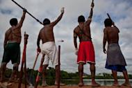 Amazonic natives symbolically occupy an earthen dam over the Xingu River in Para, northern Brazil, in June 2012 in protest against the construction of the massive Belo Monte Dam project. Some 1,600 workers resumed work Thursday after 150 indigenous people agreed to end their three-week occupation of the construction site for the dam