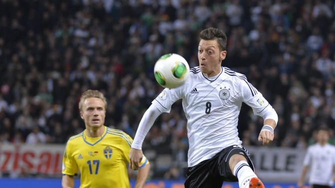 Germany's Mesut Ozil, right, is chased by Sweden's Pierre Bengtsson during the 2014 World Cup group C qualifying soccer match between Sweden and Germany at Friends Arena in Stockholm, Sweden, Tuesday, Oct. 15, 2013