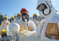 Japan's Economy, Trade and Industry Minister Toshimitsu Motegi (C), wearing a protective suit and a mask, inspects at the tsunami-crippled Fukushima Daiichi nuclear power plant in Fukushima prefecture August 26, 2013, in this photo released by Kyodo. REUTERS/Kyodo