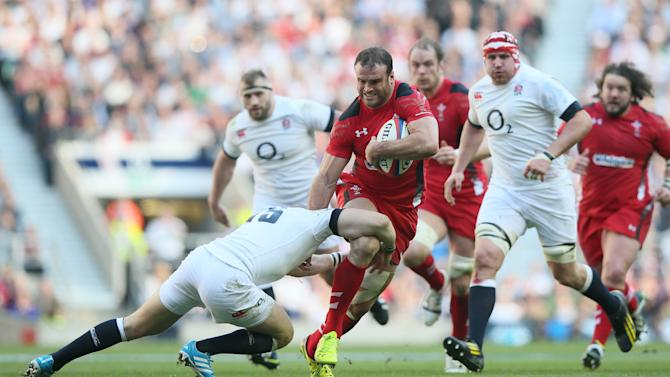 England's Mike Brown, left, goes to tackle Wales's Jamie Roberts during the Six Nations Rugby Union match between England and Wales at Twickenham stadium in London Sunday, March, 9, 2014. (AP Photo/Alastair Grant)