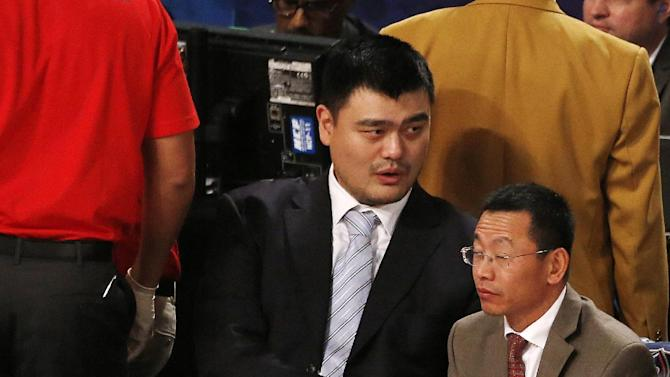 Houston Rockets' Yao Ming sits near the court during the NBA All Star basketball game, Sunday, Feb. 16, 2014, in New Orleans