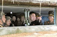 Undated photo released by North Korea's official Korean Central News Agency on August 18 shows North Korean leader Kim Jong-Un (C) looking towards the South Korean side from a watch post as he inspects island defence detachments stationed in the southwest front