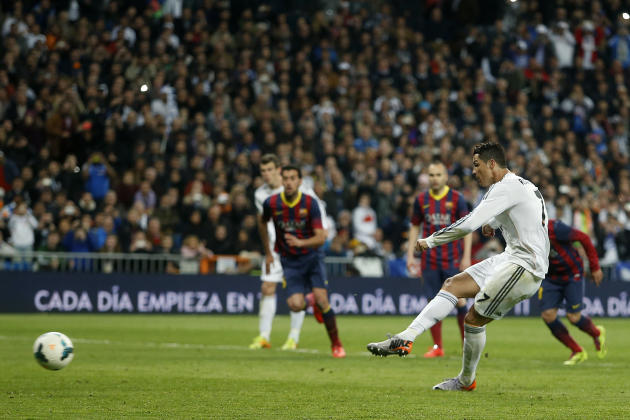 Real's Cristiano Ronaldo, right, scores his goal during a Spanish La Liga soccer match between Real Madrid and FC Barcelona at the Santiago Bernabeu stadium in Madrid, Spain, Sunday, March 23, 201