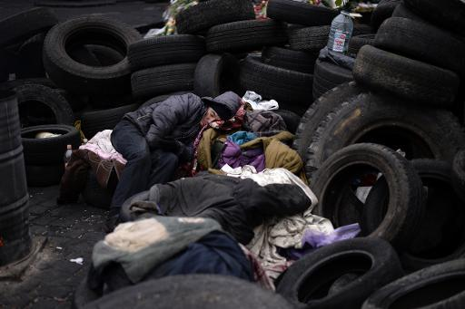 A man sleeps behind a barricade near the Dinamo stadium close to Independence square in central Kiev on March 3, 2014