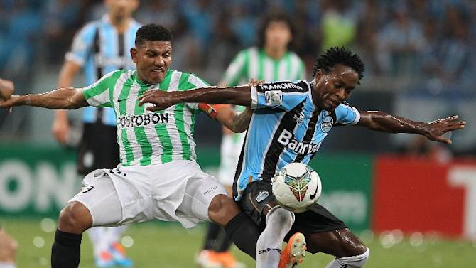 Ze Roberto of Brazil's Gremio, right, fights for the ball with Alexander Mejia of Colombia's Atletico Nacional during a Copa Libertadores soccer game in Porto Alegre, Brazil, Tuesday, Feb.25, 2014