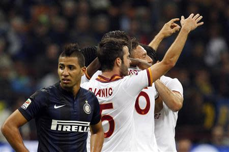 AS Roma's Totti celebrates with his team mates after scoring as Inter Milan's Taider looks on, during their Italian Serie A soccer match at the San Siro stadium in Milan
