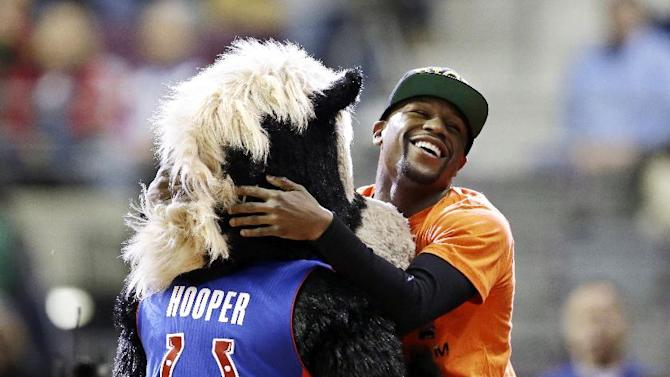 Boxer Floyd Mayweather Jr., right, clowns around with Hooper, the Detroit Pistons mascot during the second half of an NBA basketball game between the Pistons and the Chicago Bulls in Auburn Hills, Mich., Wednesday, Nov. 27, 2013