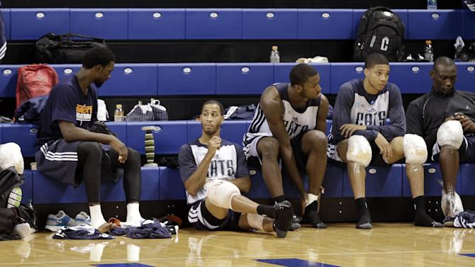 Charlotte Bobcats players, from left, Gerald Henderson, Ben Gordon, Jannero Pargo, Michael Kidd-Gilchrist, Abdul Gaddy, and Bismack Biyombo, relax on the bleachers with ice packs after practice at NBA basketball training camp in Asheville, N.C., Wednesday, Oct. 2, 2013
