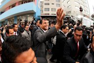 Ecuadorean President Rafael Correa (C) waves after voting a polling station in Quito on February 17, 2013. Correa declared victory in the first-round of Ecuador's presidential vote Sunday as he celebrated with thousands of supporters in the capital of the South American country