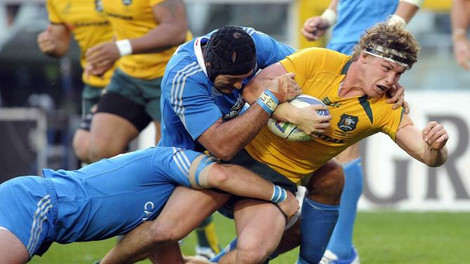 Australia's Michael Hooper is tackled by Italy's Robert Barbieri and Marco Bortolami during their Six Nations rugby union match at the Olympic stadium in Turin
