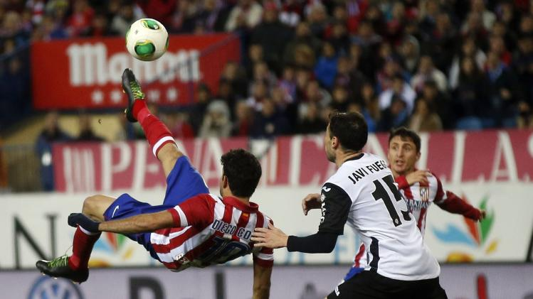 Atletico Madrid's Diego Costa kicks the ball next to Valencia's Javi Fuego during their Spanish King's Cup soccer match in Madrid