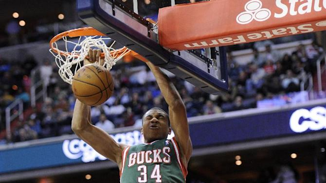Milwaukee Bucks guard Giannis Antetokounmpo (34), of Greece, dunks against Washington Wizards forward Nene (42), of Brazil, during the first half of an NBA basketball game on Friday, Dec. 6, 2013, in Washington